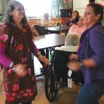 A resident and a staff member have a good time dancing