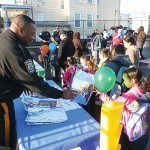 Police Officer Henry Rodgers hands out safety literature to the students