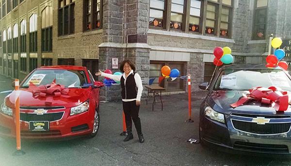 PERTH AMBOY - Ana Zevallos stands in front of the First Prize (a 2015 Chevrolet Cruze) in a Car Raffle sponsored by Saint John Paul II Parish. Tickets are on sale now and are $20 each. For more info call 732-826-1395.