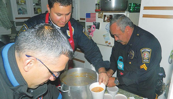 Police Officers Miguel Morales, Jorge Martinez and Harry Scheman cook a meal for the poor. Martinez was misidentified a the previous issue.   *File Photo by Henry Rodgers