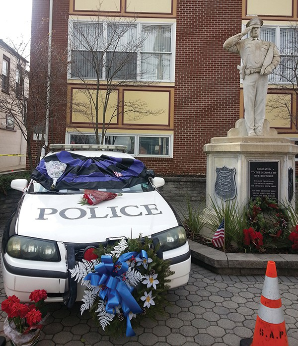 SOUTH AMBOY - A South Amboy Patrol Car stands decorated next to the statue of a Police Officer outside of City Hall. This Patrol Car has stood as a Memorial since the murder of NYPD Officers Rafael Ramos and Wenjian Liu that occurred on 12/20/14. This patrol car was decorated under the order of SAPD Chief Darren Lavigne.                                               *Photo by Carolyn Maxwell