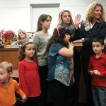 Christine Noble is sworn in by Middlesex Co. Surrogate Kevin Hoagland while some of her young family members hold the bible.