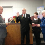 Mayor Fred Henry is sworn in by City Attorney John Lanza as his wife, Linda and his mother, Ann hold the bible.