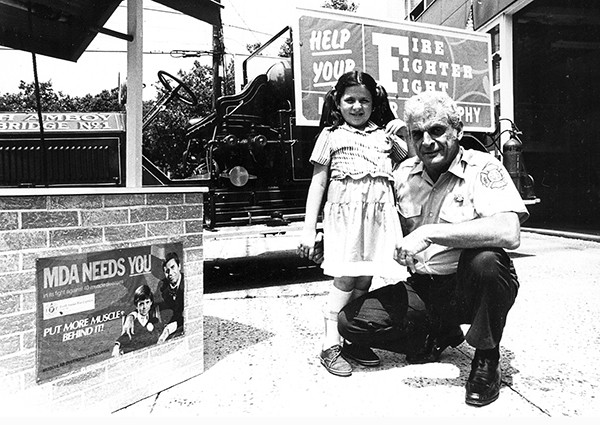 PERTH AMBOY - Perth Amboy Firefighter John Siberry poses for a photo with a young girl beside the poster for the Muscular Dystrophy Telethon featuring Jerry Lewis. *Photo Courtesy of John Siberry This Photo was restored under a grant for the Kearny Cottage Archiving project by the Middlesex Cultural and Heritage Commission