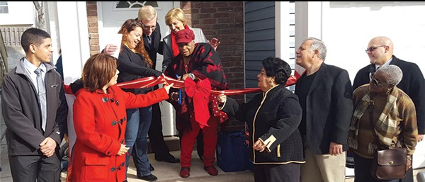 PERTH AMBOY - E. Dorothy Carty-Daniel, fifth from the right, Board Chair of P.A.R.T.N.E.R. cuts ribbon for Mercado family. From left: John Martin, Project Supervisor, of Morris Habitat of Human; Mayor Wilda Diaz; Noris Mercado, Douglas Dzema, Executive Director of P.A.R.T.N.E.R.; Blair Schleicher Bravo, CEO of Morris Habitat for Humanity; Delia Yili, Fernando Gonzalez, Josephine Smith, and Hector Motta, P.A.R.T.N.E.R. board members. *Photo Submitted