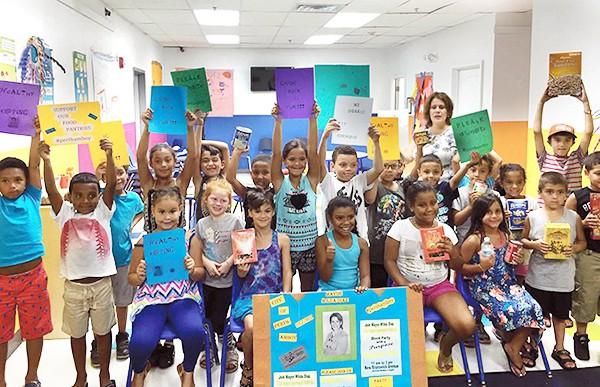 "PERTH AMBOY - Perth Amboy Mayor Wilda Diaz (back row, right side) and students from I Excel Child Care Center at 165 Washington Street hold signs and food items to remind everyone to attend the City's ""Block Party with a Purpose"" on Saturday, August 27 beginning at 11 a.m. The community can celebrate together and donate non-perishable food items to help restock the shelves of the City's food pantries. Adults and children of all ages are invited to New Brunswick Avenue, between Madison and Maple Streets, for the ""Block Party with a Purpose"" that includes free hot dogs, inflatable slides and rides, a balloon artist and performances by dance groups. Perth Amboy's C-Town Supermarket, Quisqueya Foodmarket, Supremo Supermarket and Tropical Supermarket are giving the food drive a big boost by donating products. The ""Block Party"" is sponsored by the Perth Amboy Business Improvement District (BID), the City's Recreation Department, Renovation House, Lighthouse Worship Center, and the St. Vincent de Paul Food Pantry. *Photo by the Perth Amboy BID"